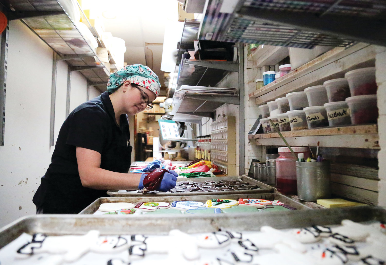 Ashley Lawrence decorates sugar cookies at Rheinlander Bakery.