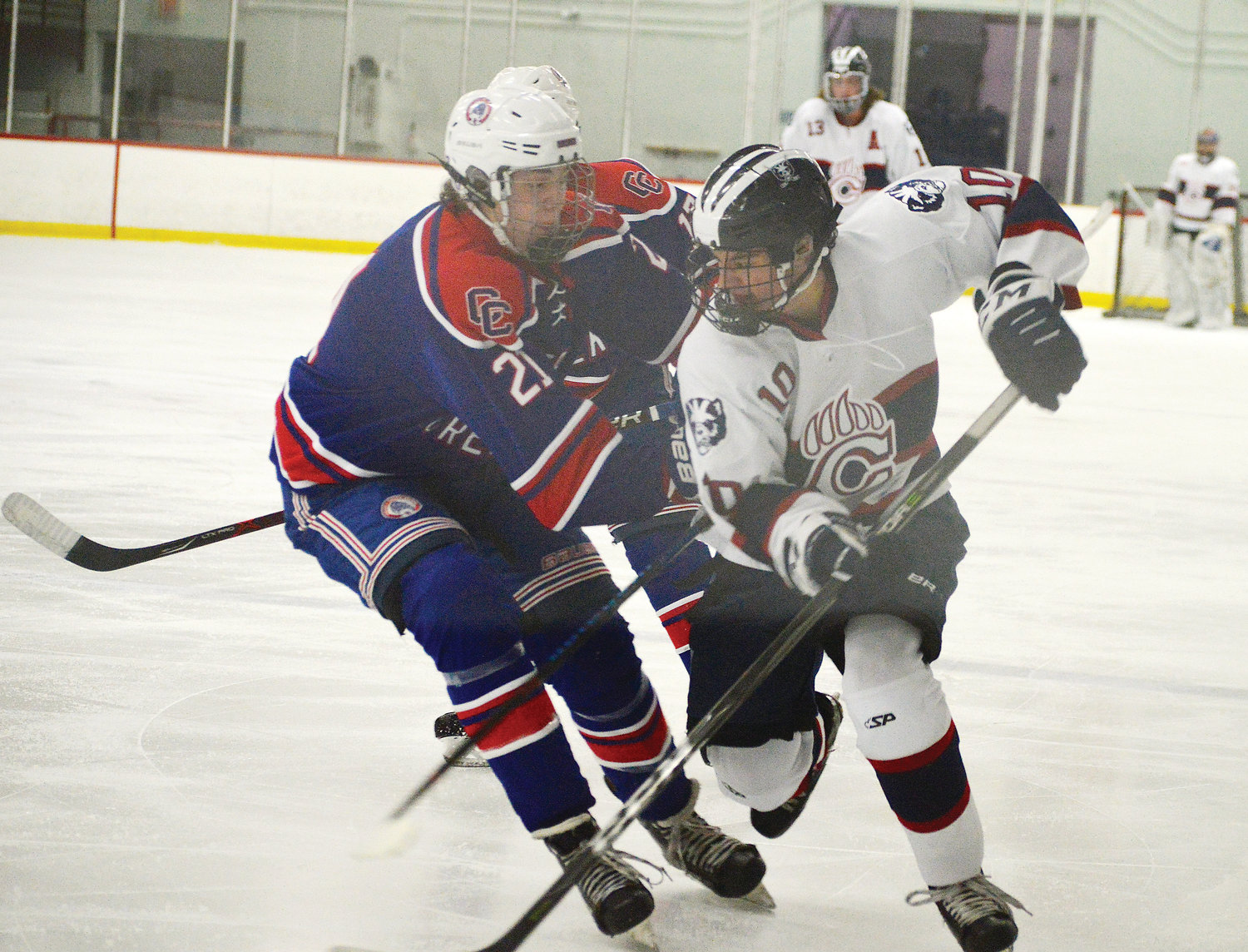 Cherry Creek defenseman T.J. Ranone (21) tries to knock Chaparral's Dylan Florit (10) away from the puck during the Dec. 21 game at Family Sports Center.  Florit had a goal and assist in the Wolverines' 3-1 victory.