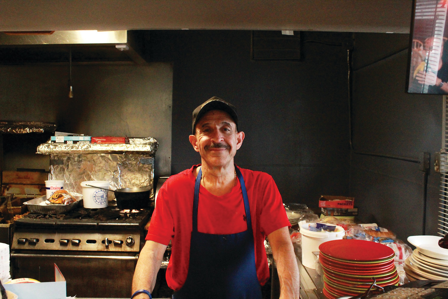 Nick Andurlakis poses behind the counter of Nick's Cafe. The restaurant is known for its Fool's Gold sandwich.
