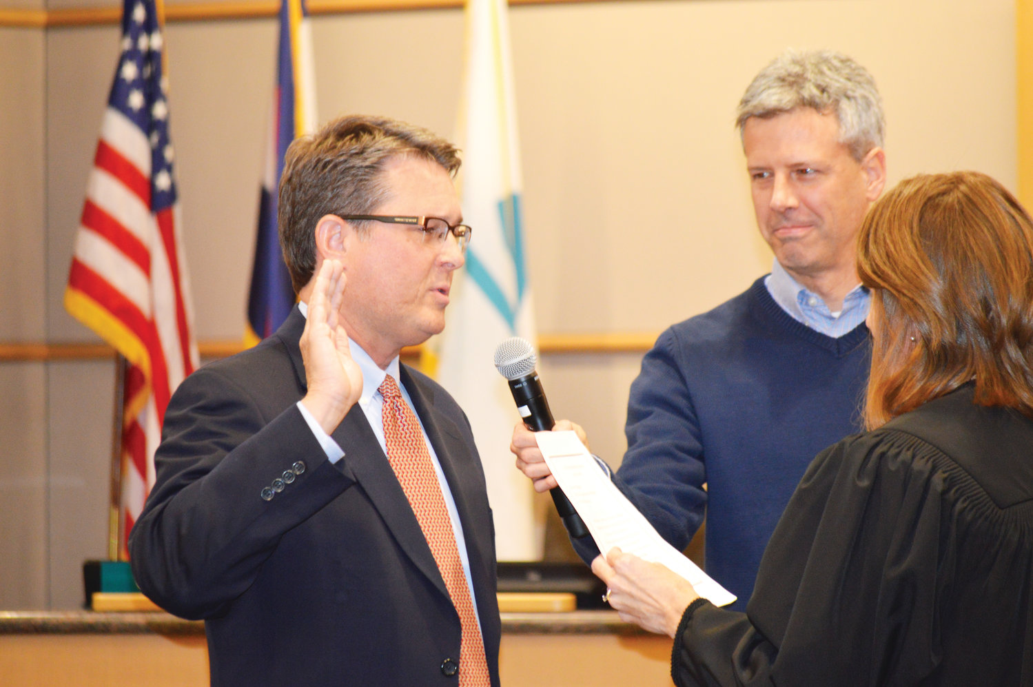 Newly named City Councilor Jon Voelz swears his oath of office Jan. 28 in front of Municipal Judge Tiffany Sorice while his partner, T.C. Hosna holds the microphone.
