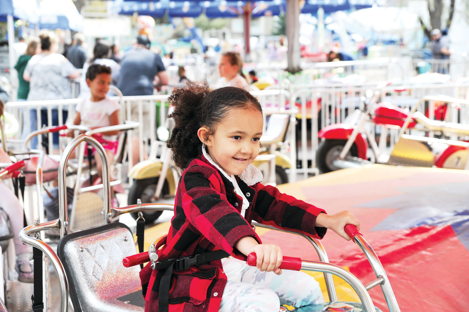 Leilani Monroes, 4, of Northglenn, prepares to depart on a children's motorcycle ride, which was part of this year's annual Food Truck Carnival, at the Northglenn Community Center.