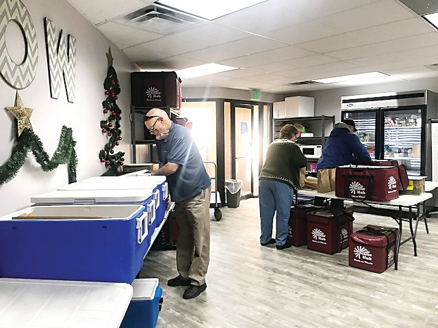 Volunteers prepare their day's deliveries at the Northglenn offices of Senior Hub. The volunteers will deliver meals daily to 80 clients in Northglenn, 103 in Westminster and 148 in Thornton.