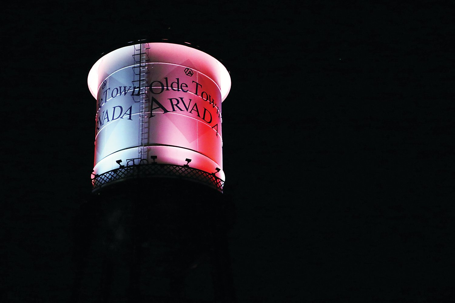 Olde Town Arvada water tower lit up in Pomona High School's colors.