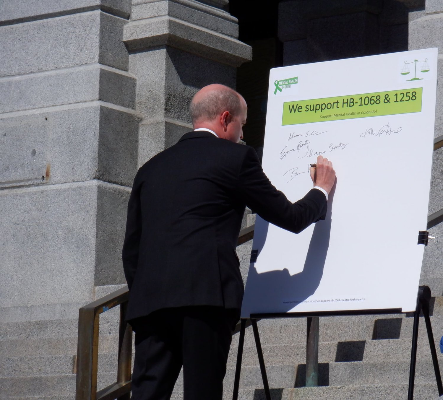 17th Judicial District Attorney Brian Mason signs his name to show support for bills in the state legislature that aim to provide Coloradans with more mental health resources at a May 12 press conference.