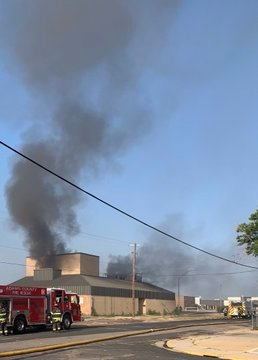 The theater building at the former campus of Adams City High School catches fire July 15.