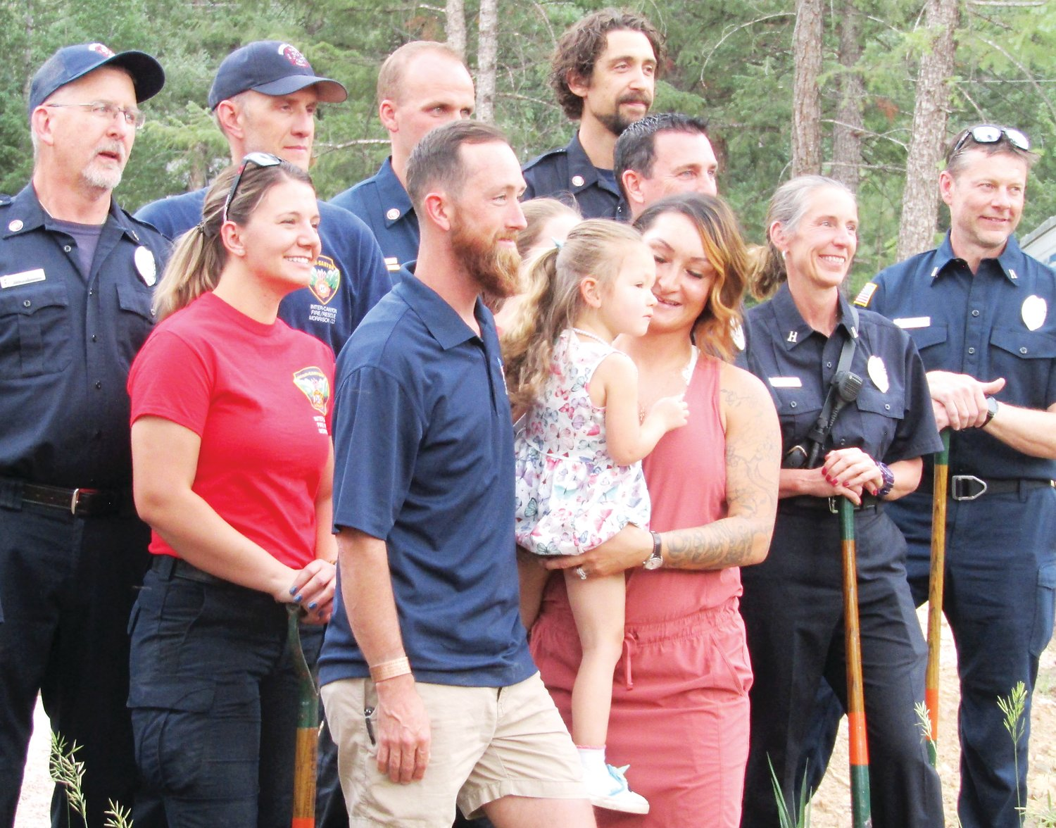 Joel, Adyline, 3, and Tasha Booth stand with Inter-Canyon Fire volunteers at the groundbreaking ceremony.