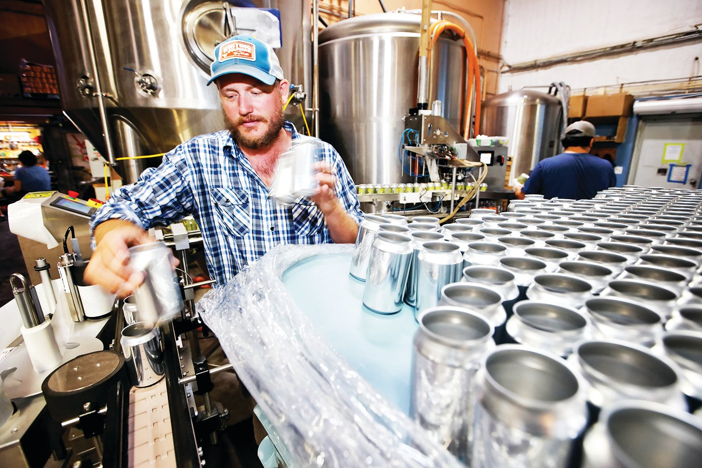Head Brewer Danny Wilson labels blank cans with Dirty Hippy stickers at Palisade Brewing Company in Palisade, Colo., on July 28. Because of an international shortage of aluminum containers, Palisade Brewing has been unable to purchase printed cans blank cans individually wrapped with labels.
