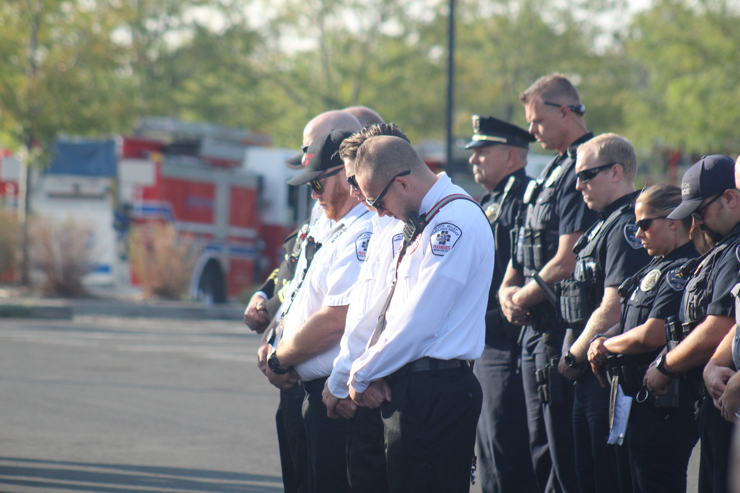 Members of the Platte Valley Ambulance Service and Brighton police reflect during the 20th anniversary of 9/11 program outside Brighton City Hall.