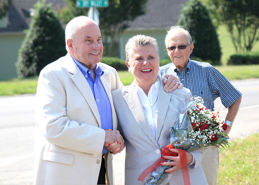 CLEVELAND MAYOR EMERITUS Tom Rowland, left, congratulates Lynn DeVault during an earlier ceremony in which a portion of the roadway at the north end of the Cleveland Jetport complex was named in her honor. Rowland now succeeds DeVault on the Cleveland Municipal Airport Authority. In the background is Verrill Norwood.