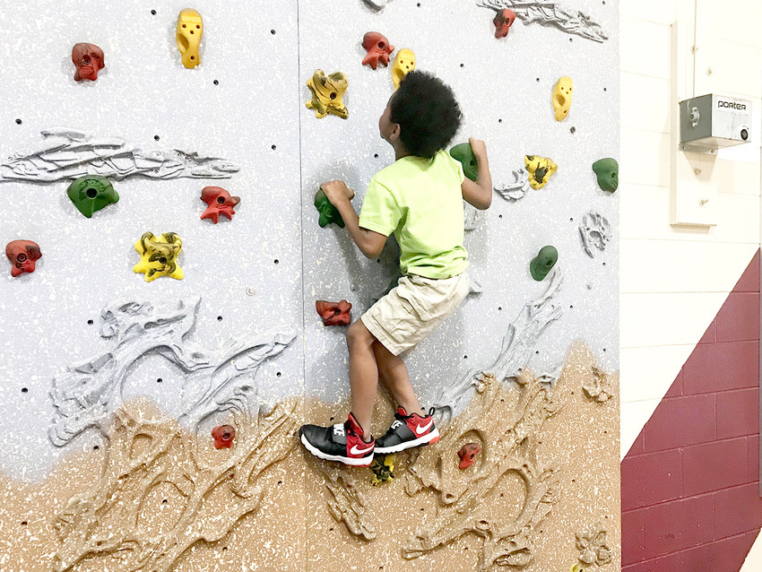 Student Nigel Watkins enjoys challenging a low climbing wall, one of many activities available during the evening at Blythe-Bower Elementary's registration celebration.