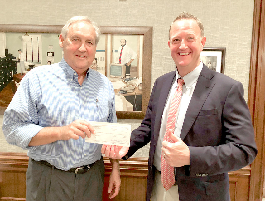 DAVID BECKLER of the Cleveland High School Alumni Association, left, accepts a donation of nearly $16,500 for the Cleveland High School Alumni Walk from Toby Pendergrass, representing the Allan Jones Foundation. The foundation matched the nearly $16,500 which had been raised by close to 150 people.