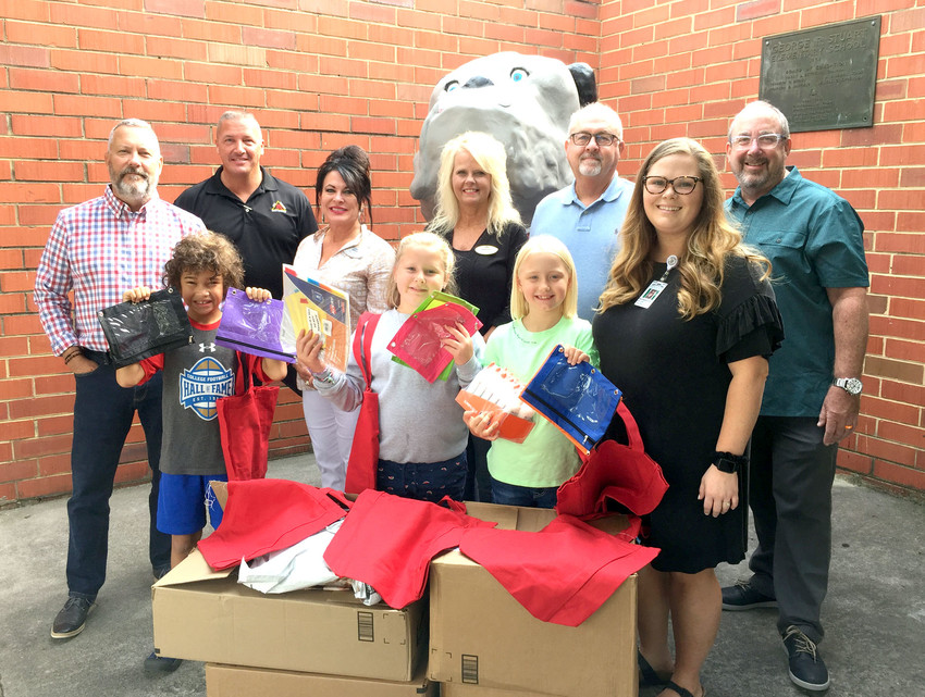 STUART ELEMENTARY recently received a generous donation from Bender Realty. Representatives brought school supplies for incoming kindergarten students.  In the front row, from left, are students Eliot Fuller, Gracie Gray and Natalie Higgins, along with Savannah Shell, Family Involvement coordinator at Stuart. In the back row are Bender representatives Jim Metzger, Ricky Tallent, Julia Tallent, Sharon Parker, Jim Workman and Robert Bradney.