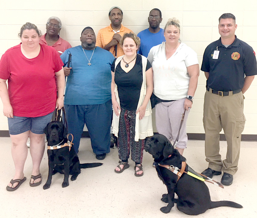 LEARNING ABOUT FIRE safety was the main focus of the Southeast Chapter of the National Federation of the blind's August meeting. First row from left are: Christy O'Dell, president with guide dog, Wiggles; Mandy Dixon; Sharon Warren, social media with guide dog, Avery; and Lieutenant Craig Foote, guest speaker. Second row from left are: Faheem Bengazi, vice president; Daniel Henry; Jackie Holmes; and Governor Staten.