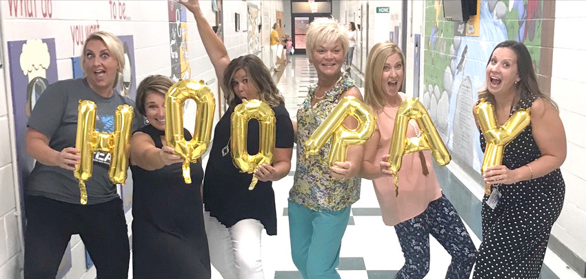 Missy Chastain, Dawn Puckett, Nikki Mason, Angie Davis, Abbey Duncan, and Adelia Hall shouted Hooray and cheered for students as they walked in the door at Oak Grove.