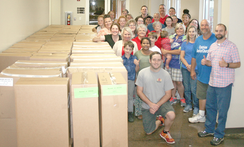 THE CREW of the 2018 Packing Party gathered around its massive bounty of shoes, socks and shoelaces for this year, knowing they beat last year's numbers. For 2018, the drive raised 2,732 shoes compared to last year's 2,652. For socks, it raised 7,508 compared to last year's 3,000.