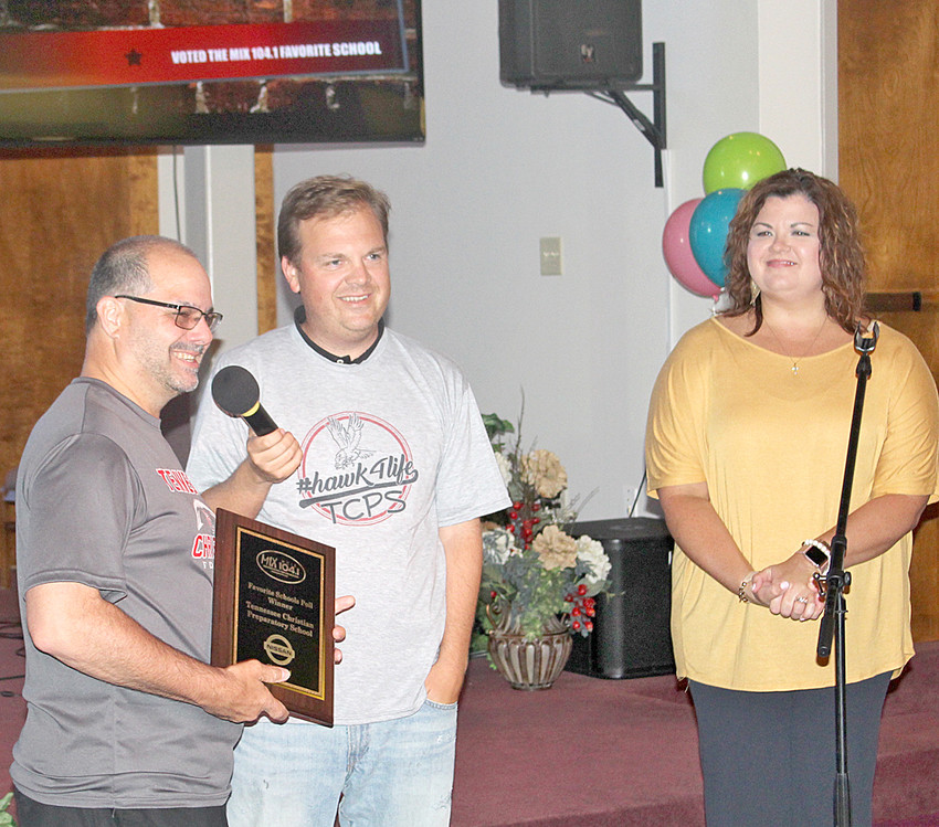 "DR. JIMMY HARPER, left, president of Tennessee Christian Preparatory School, accepts a plaque from WCLE 104.1 FM's Steve Hartline, middle, and Bridget Forrester. TCPS selected as the area's ""Favorite School"" during an online poll conducted by the station."