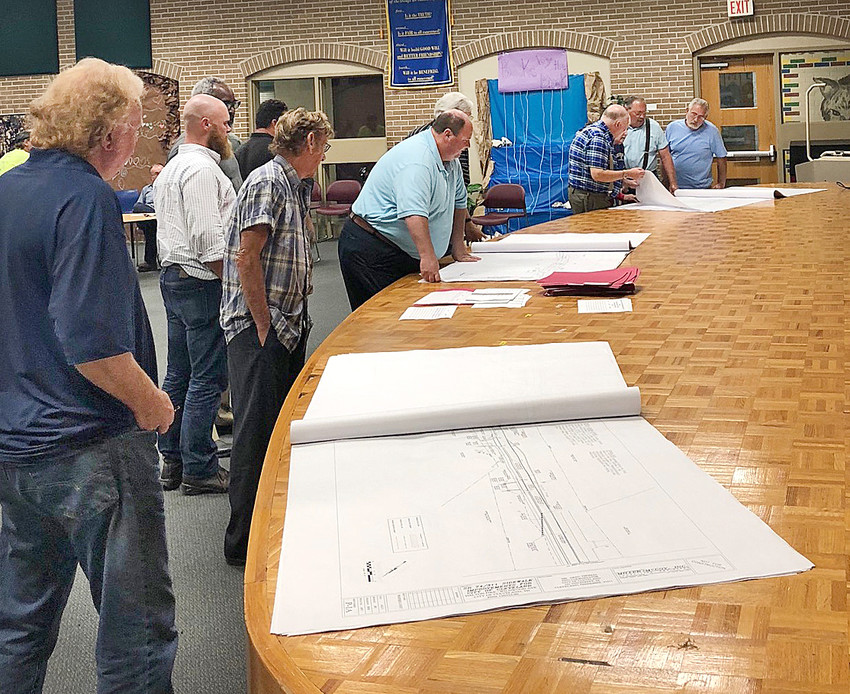 CITY RESIDENTS and officials examine site plans that show how a future sidewalk construction project in the Dalton Pike/Wildwood Avenue area will affect right of way areas near their properties. Some residents questioned whether new, as well as rehabilitated sidewalks, will improve their area.