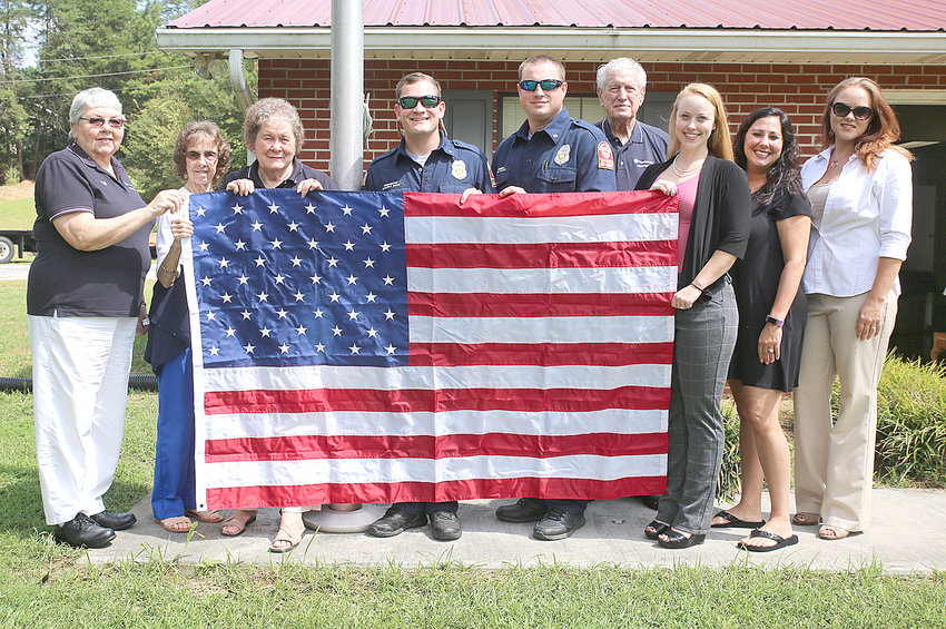WOODMEN LIFE REPRESENTATIVES replaced the American flag at Bradley County Fire-Rescue Station 5, Prospect, on Wednesday, Sept. 12.  From left are Eula Kile, Christine Miller, Joyce Johnson, Firefighter Dakota Ream, Engineer Wally Taylor, W.W. Johnson, Rose Jaggers, Courtney Witherow and Kodi Mann.