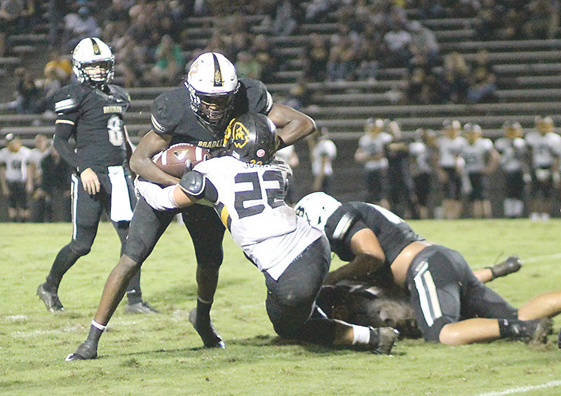 BRADLEY CENTRAL'S Tray Curry (12) plows over over a McMinn County defender in last Friday's Bear victory. The 6-foot-5 sophomore NCAA D-I prospect was used primarily in the backfield last week, in a new wrinkle to the Bear offense.