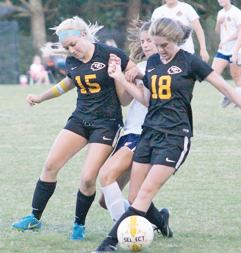 WALKER VALLEY sophomore Ashley Eulo (center) is barricaded and fouled by a pair of McMinn County players in a battle for first place in Tuesday's District 5-AAA battle. The Lady Cherokees pulled away late for a 3-0 victory in Athens.