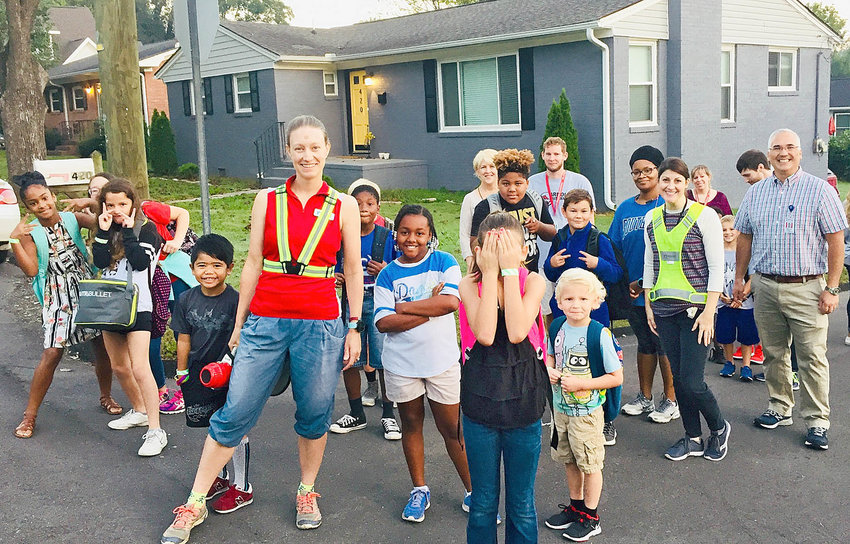 PART OF THE GROUP of participating students, teachers and parents, including Bike/Walk Cleveland Chairman Gina Simpson, center, and Principal Michael Chai, right, pose for a fun photo during the 2018 Walk to School Day event.  The event is a way for students to share some time with classmates and family, see the school from a different perspective and get a little exercise.
