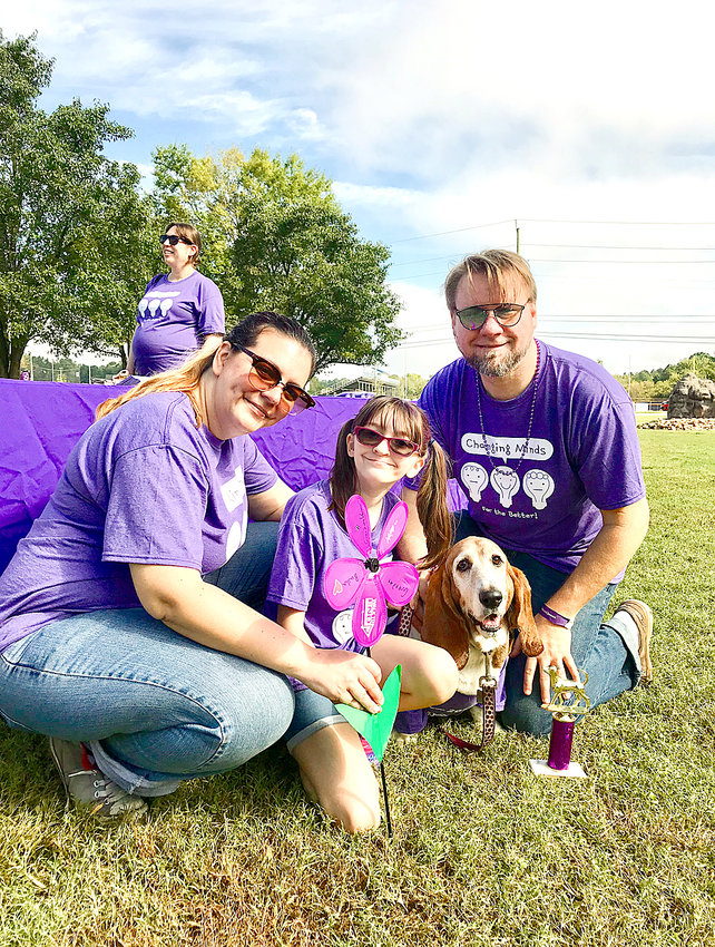 "RYAN FARICELLI, right, poses for a photo with his family at the 2018 Walk to End Alzheimer's at Greenway Park. From left are Ryan's wife, Carie Varner-Faricelli, daughter, Dakota, family dog ""Trixie the Memory Hound"" and Ryan."