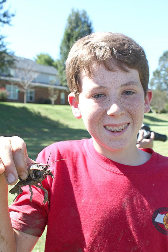 "The seventh- and eighth-grade class at Bowman Hills School, with the help of Carl Williams from the Tennessee Wildlife Resource Agency, uncovered a rare blue crayfish on a ""field"" trip Oct. 11.  Students learned how to carefully excavate the hole of a burrowing crayfish and extract several of the beautiful creatures from the mud in the field near their school in Cleveland. Classroom teacher Valerie Hunt shows the blue crayfish close up. A student Tanner Walker was the first student to find the elusive species during the adventure."