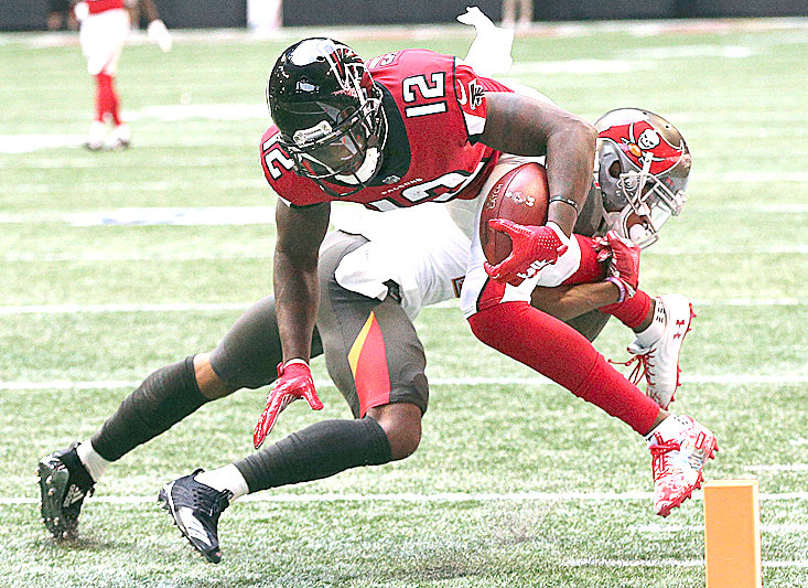 ATLANTA FALCONS wide receiver Mohamed Sanu dives for the end zone past Tampa Bay Buccaneers safety Justin Evans in the first quarter Sunday, in Atlanta.