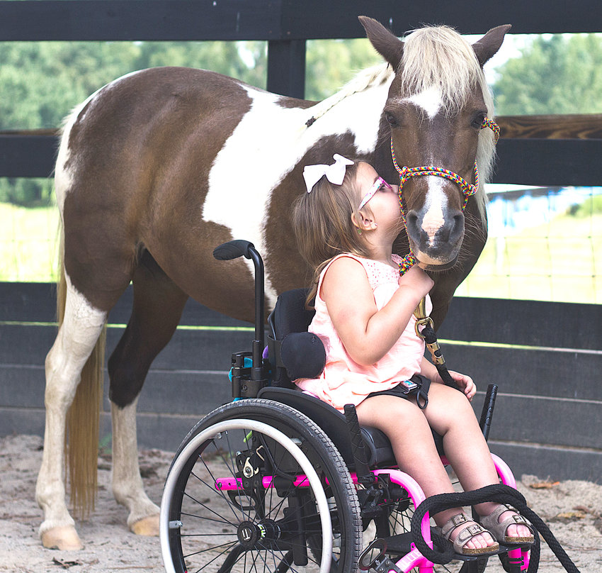 """THERE ARE A NUMBER of """"love affairs"""" a the Mending Arrow Ranch. Above, young Paisley Carroll places a well-targeted kiss on the cheek of the ranch's pony, Cupcake. They participate in the Brave One program."""