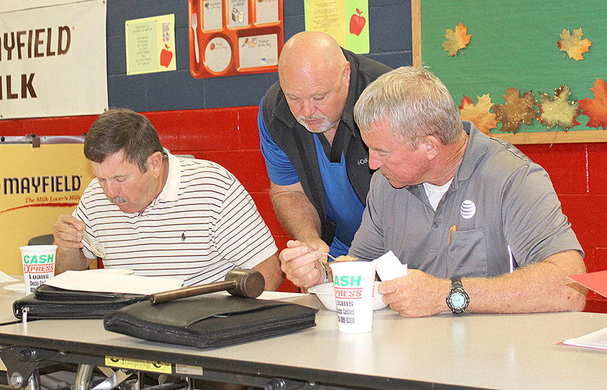 POLK COUNTY BOARD of Education member Stan Howard, center, shares some numbers with fellow member David Green, left, and School Board Chairman Mark Williams. Howard has been working closely with Director of Schools Dr. James Jones on heating and air needs for the school system.