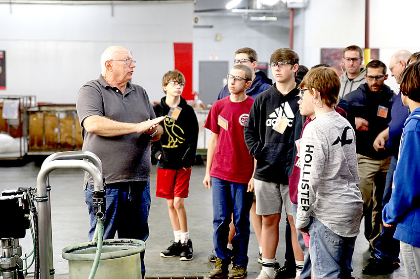 STEVE KNIGHT, process engineer at Polartec, explains a part of plant operations to a group of students from Cleveland High School.