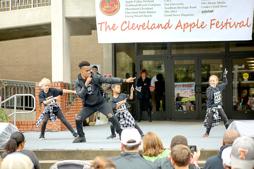 RYAN ROBERTS FROM RAW Art Dance & Entertainment, center, leads a group of his students in a dance at the 2018 Apple Festival. From left are Haylyn Helms, Roberts, Kenall Boyd and Abby Buckley. The Cleveland Apple Festival continues today, 1 to 6 p.m. The Little Miss Apple Blossom competitions begin at 4 p.m.