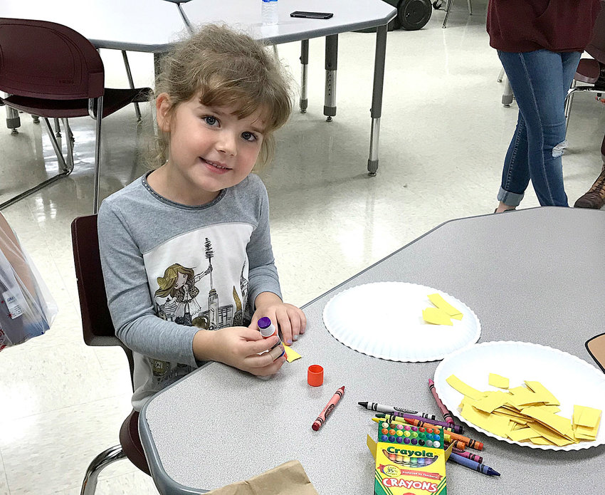 Skylar Palmer creates a scarecrow at the 2018 Blythe-Bower Elementary Fall Harvest Hoedown's Kids' Crafts station.