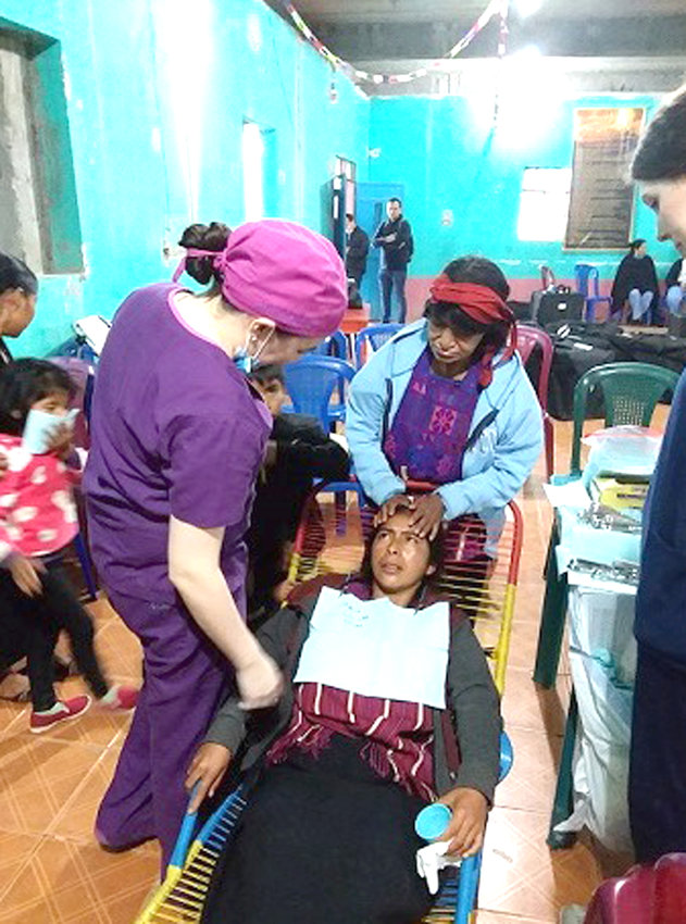 Jessica Mitchum, trip alum now enrolled in dental school at UAB, is shown here assisting Dr. Linda Flor, Huehuetenango dentist, helping a patient while her mother prays.