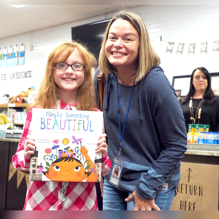 At left, April Cole from Eaton Corporation takes a picture with fourth-grader Sonya Stedman before heading to Mrs. Gaskill's class at Taylor Elementary to read a book. Above, after a reading to students at Taylor Elementary, Bradley County Sheriff Steve Lawson talks with Nate Mathis' fifth-grade class about his role in the community.