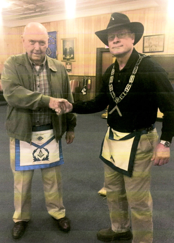 HERB STAFFORD, left, is presented with a 50-year membership apron in the Masonic Lodge by Bruce Bancroft, right, Master of Lodge 134 in Cleveland. Herb entered the Masonic Lodge in October 1966 in Virginia, and later transferred to the Cleveland lodge.