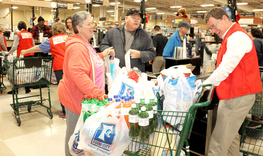 """FROM LEFT, Sandy and Tony Cunningham chat with their """"celebrity bagger,"""" United Way of the Ocoee Region President and CEO Matt Ryerson, during Tuesday's """"Celebrity Bagger Event"""" at Food City. Volunteers worked from 10 a.m. to 6 p.m. at the Ocoee Crossing shopping center store."""