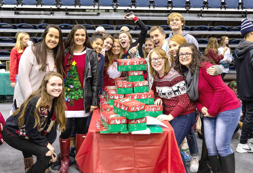 Students from Dr. Sherry Kasper's Gateway class pose with their Operation Christmas Child shoeboxes during Lee's annual Pack 'n' Stack event.