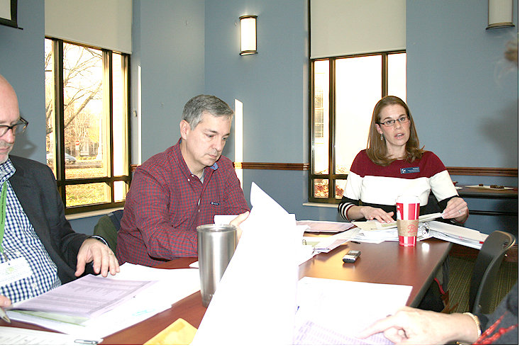 LIBRARY DIRECTOR Andy Hunt, left, and board member John Coats, center, hear the Ocoee River Regional Library report from Liz Schreck at Tuesday's meeting of the Cleveland Bradley County Public Library Board.
