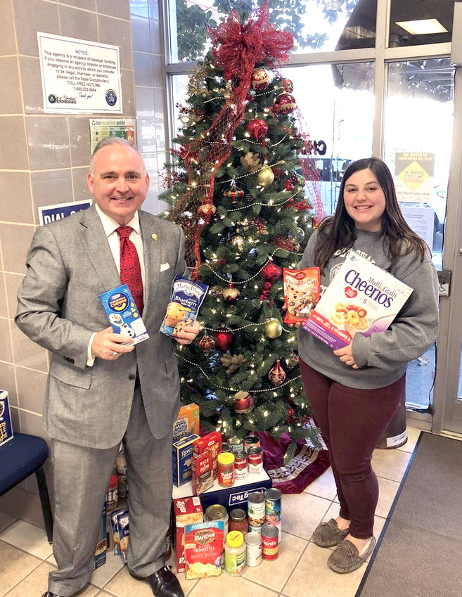CLEVELAND MAYOR Kevin Brooks and Cleveland Finance Department Deputy Clerk Lindsey Hawkins hold items donated to the city's food drive, which will benefit victims of domestic violence. Donations will be collected through Dec. 20.