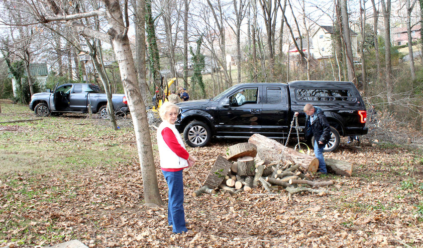 LIZ NORWOOD, widow of the late Bill Norwood, watches as members of the U.S. Army and U.S. Air Force, work to clear some dangerous trees and brush at the rear of her home in northeast Cleveland. The project was an example of military branches coming together during the holidays, to help someone in need.