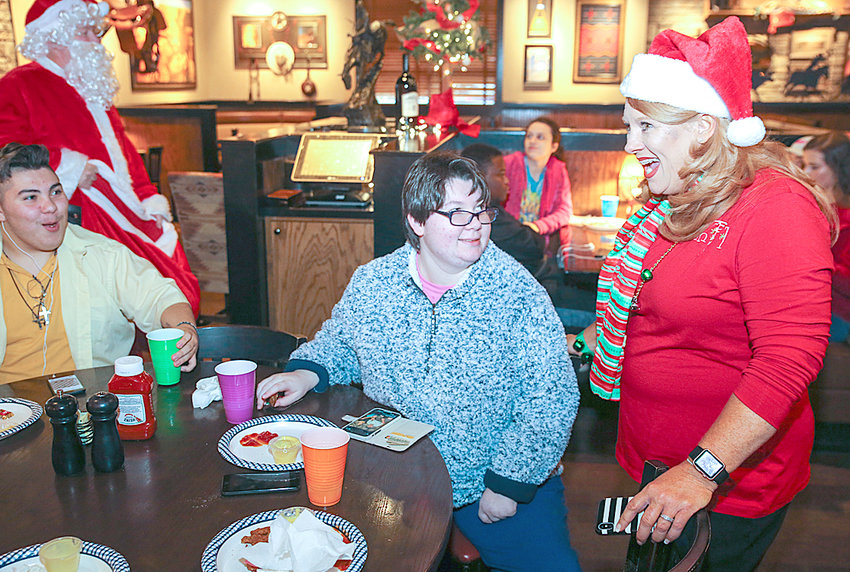 LONGHORN STEAKHOUSE MANAGING PARTNER Leeann Pulliam, right, speaks with CHS student Sarah Dale during their Christmas meal on Friday. LongHorn Steakhouse has been hosting the CHS Christmas meal for five years now. The kids got to enjoy chicken fingers and fries, cake and a special visit from Santa Claus. Also shown is Alex Hernandez, left.
