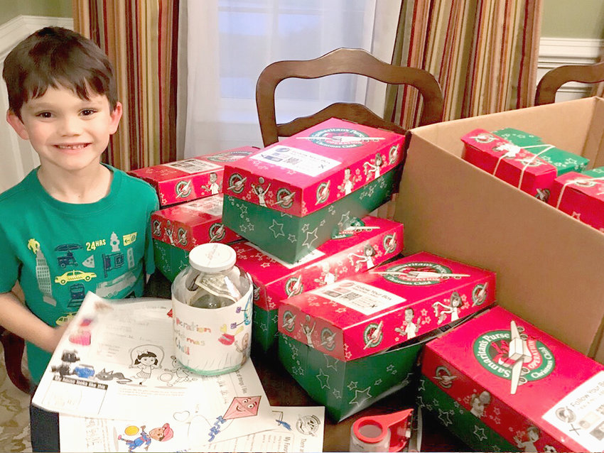 LITTLE Joseph Simpson, above left, who is 6 years old, recently held an Operation Christmas Child-themed birthday party. Instead of having guests give gifts to him, he asked for donations to help other children around the world. His mom, Megan Simpson, said it was just something her son wanted to do. Below left, Joseph, with tremendous pride, prepares to donate nine Operation Christmas Child boxes and $115 during this year's annual OCC collection drive at First Baptist Church. He is joined by his mother Megan, 4-year-old brother Matthew and 1-year-old brother Ethan.