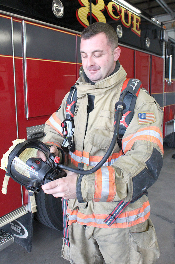 """BRADLEY COUNTY Fire-Rescue Lt. C.J. Davis demonstrates how to """"click in"""" the breathing regulator to the mask used with the new air-paks. Once clicked in, a row of small LED lights show the firefighter how much air is left in the tank."""