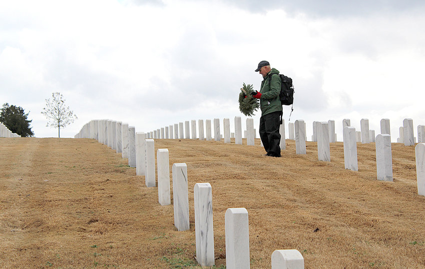 A MAN ponders before laying a wreath at a grave marker during a Wreaths Across Chattanooga ceremony held Saturday at Chattanooga National Cemetery.