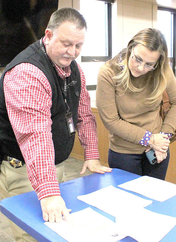 DEWAYNE SCOGGINS with the Bradley County Sheriff's Office goes over bid documents related to a new or upgraded control panel with Commissioner Erica Davis, following Monday's Bradley County Commission voting session.