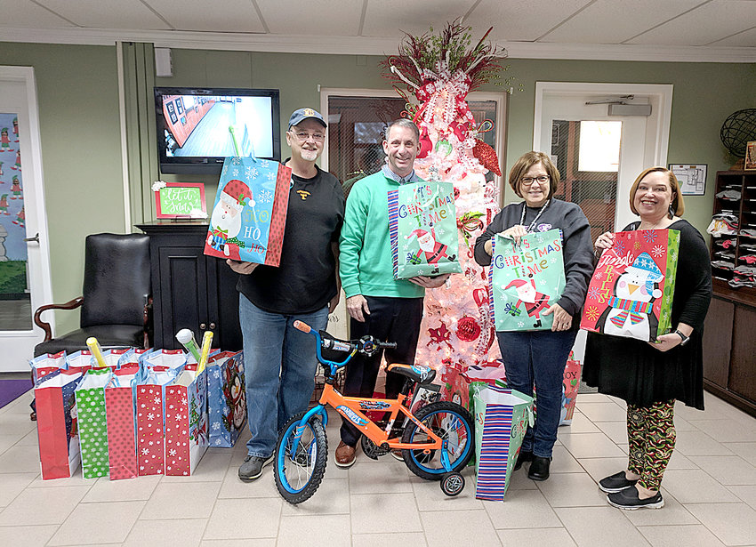 McDonald/Black Fox Ruritan was proud to provide a little Christmas cheer to some well-deserving children at Prospect School. From left are Ruritan President David Swafford, Principal Steve Montgomery and secretaries Shelia Robinson and Lisa Newman. McDonald-Black Fox Ruritan delivered 50 Christmas gift bags to support families at Black Fox Elementary. The bags are filled with neat gifts and activities that children love.