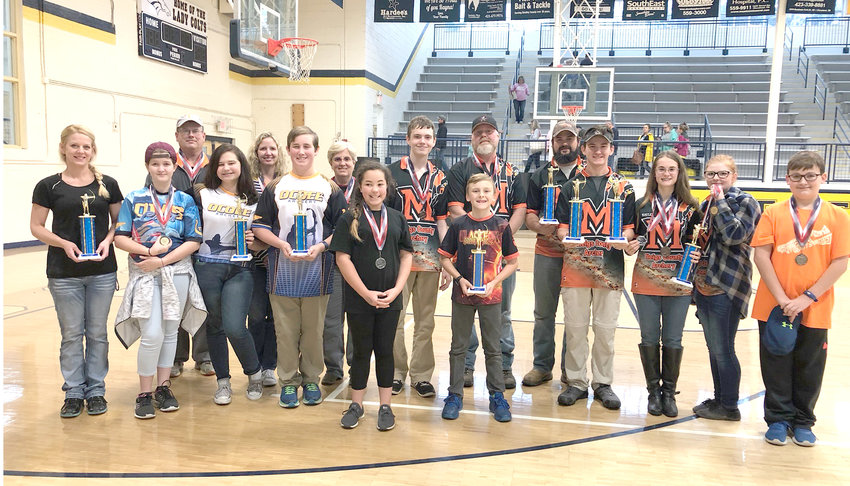 Some of the adults involved in the tourney posed with a few of the student winners: Sawyer Hammond, first place, elementary boys; Kane Dawson, second place, elementary boys; Noah Dycus, third place, elementary boys. Braelyn Taylor, third place, elementary girls; JimBo Canida, first place, middle school boys; Brylie Webb, first place, middle school girls; and Tempe Wright, third place, middle school girls.