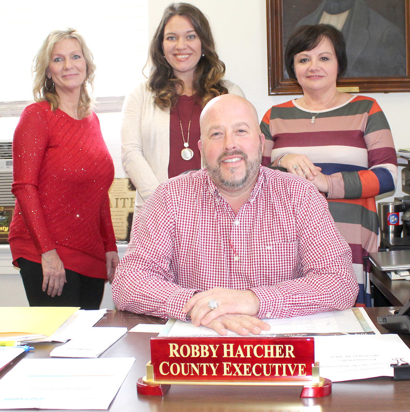 NEW POLK COUNTY EXECUTIVE Robby Hatcher, seated, is enthusiastic about his new administrative staff. When he took office in September, the entire staff of former Executive Hoyt Firestone had departed. Hatcher's new hires include, from left,  Linda Crockett, budget assistant; Catrice Lowe, accounts and budget director; and Lois Potts, personal secretary.
