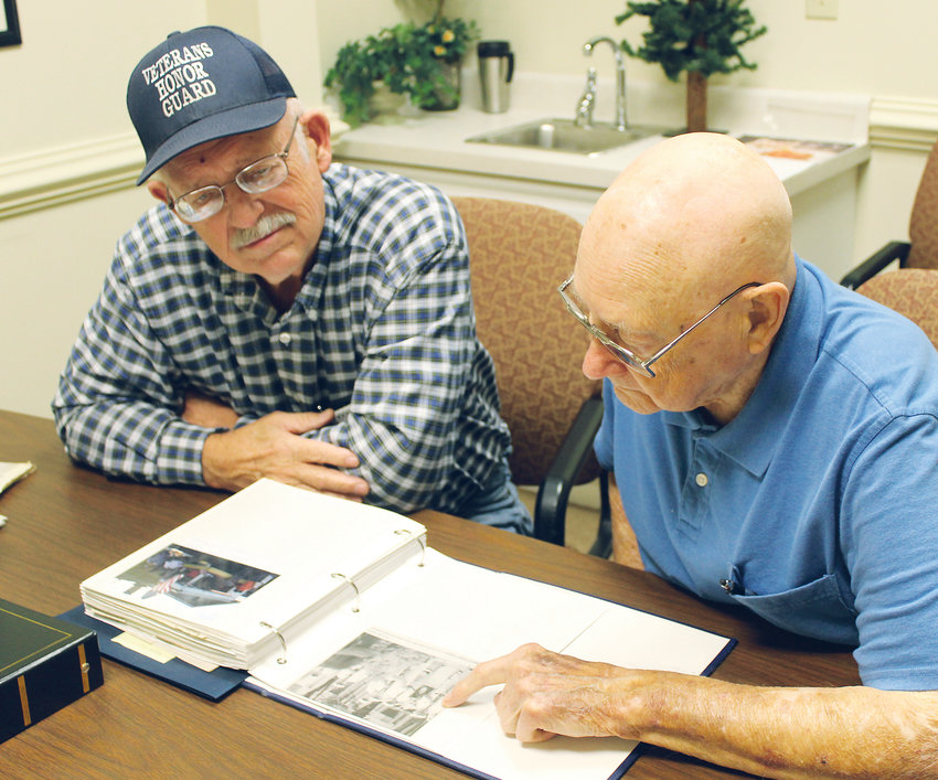 FUNERAL HONOR GUARD members John Thomason, left, and Carl Zurcher glance through a portfolio of photographs from the 116 ceremonies the unit attended in 2018. The two are attempting to spread the word that Honor Guard services are available to anyone who served in active duty military, or in the Reserves or National Guard.